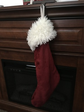 An empty red Christmas stocking hanging on a fireplace.