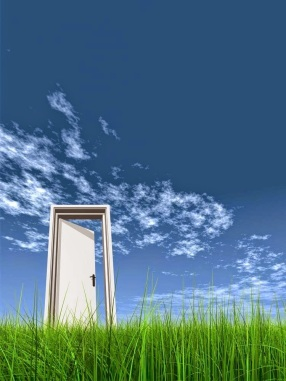 A simple doorway to the blue sky on green grass.